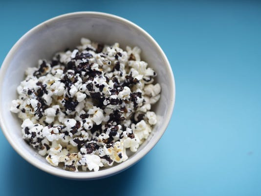 Do you struggle to keep your hand out of the popcorn bowl after dinner? Here's how to nix nighttime snacking. (Daily Record/Sunday News -- Kate Penn)