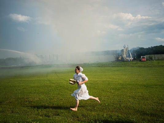 A girl runs from the barn fire in Mount Joy Township