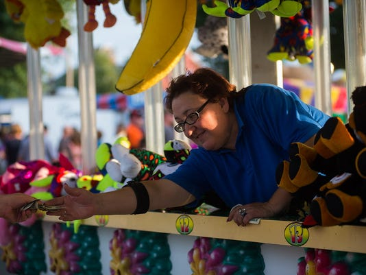 Kim Meyers takes money from a customer who has stepped up to the water game, Rising Waters, at the Littlestown Fireman's Carnival on Aug. 6, 2014.