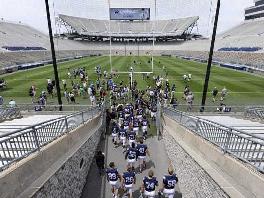 Wearing jerseys that no longer have their names on the back, players with the Penn State football team enter Beaver Stadium to be interviewed for media day in State College on Thursday, August 6, 2015.
