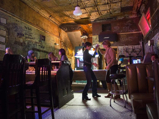 Darla Kipp, left, and Kathy Goranson, both of Johnston, dance to Johnny Cash at the Locust Tap in Des Moines.