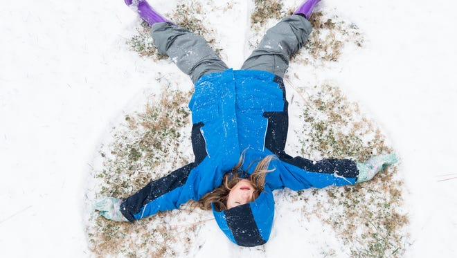 Kayden Randolph creates a snow angel while playing outdoors with her family on Tuesday, January 16, 2018.