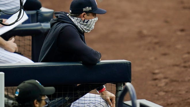 New York Yankees manager Aaron Boone wears a mask as he stands in the dugout during the third inning in Game 4 of a baseball American League Division Series against the Tampa Bay Rays, Thursday, Oct. 8, 2020, in San Diego.