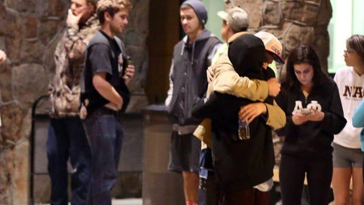 Students embrace outside a hospital emergency room