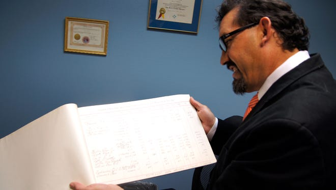 Grant County Tax Assessor Raul Turrieta displays a ledger on Wednesday showing handwritten real estate and personal taxes from 1893, part of the county records he found in the basement of the courthouse.
