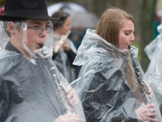 Band members march beneath ponchos Friday during De