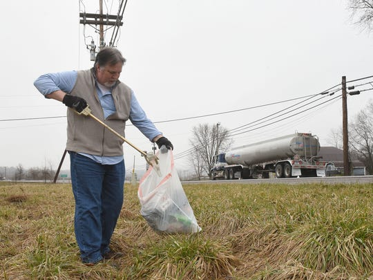 Kenn Kiser, founder of Clean Up Litter In Coshocton, picks up trash along County Road 1A near the intersection with US 36.