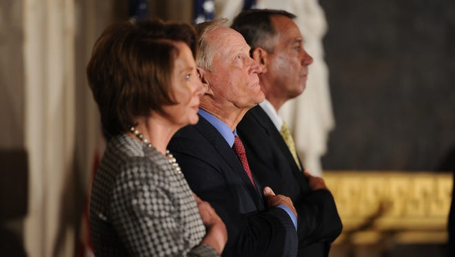 Rep. Nancy Pelosi, D-Calif., Jack Nicklaus and House Speaker John Boehner, R-Ohio, listen to the National Anthem at a ceremony where Nicklaus received the Congressional Gold Medal.
