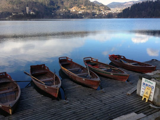 Traditional gondola-style wooden rowing boats rest near the shore of Lake Bled. Those who arrive by boat can reach the island's church by ascending 98 steps.