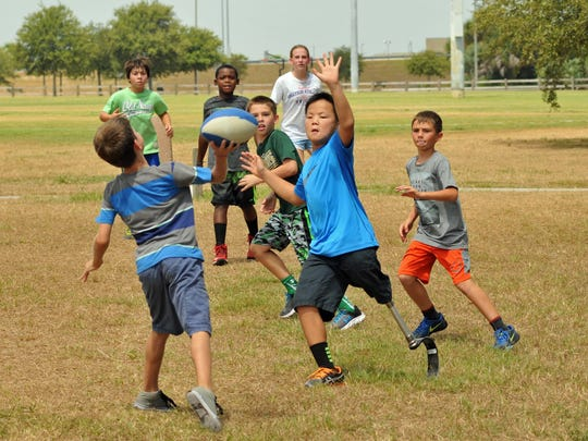 Kids play football in the dry grass at Viera Regional