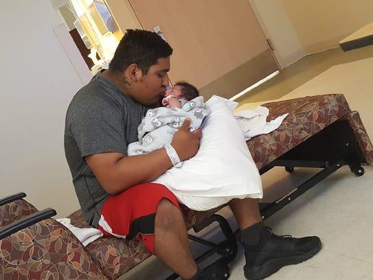Gilbert Sierra III kisses his youngest son Damacio