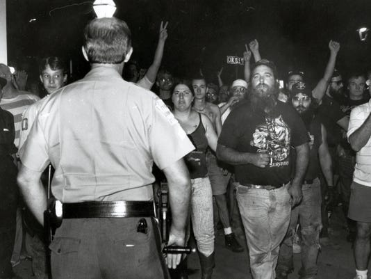 A mob stands in front of a Hanover borough police officer during riots in Hanover that were sparked from racial tensions in July 1991. (File)
