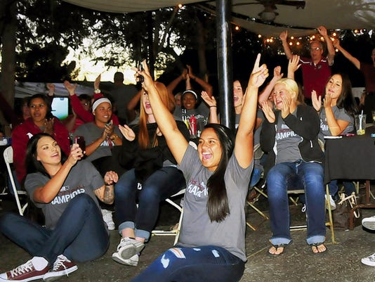 Jaime Guzman/For the Sun-News  The New Mexico State softball team reacts to the announcement of their NCAA Tournament game against Minnesota during the NCAA Tournament selection show Sunday night at The Game Sports Bar and Grill.