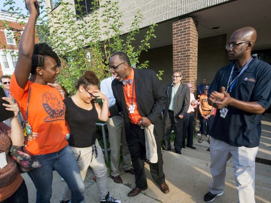 From the left, school board member Sandie Walker, walks embarrassed freshman Laurie Haigood past George Fitch, William Penn Senior High School assistant principal. Hall monitor Jerald Proctor is at right. School staff and community members cheered and clapped as the freshmen arrived at school for the first day.