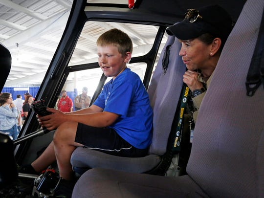 Chase Zitzelsberger, 8, of Stockbridge, checks over the controls of an Airbus EC120 helicopter with U.S. Customs pilot Barbie Moorhouse during a special tour with other Make-A-Wish children Saturday, July 30, 2016, at Oshkosh.
