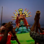 Civic workers immerse an idol of Hindu goddess Durga into the Brahmaputra River in Gauhati, India, on, Oct. 4.