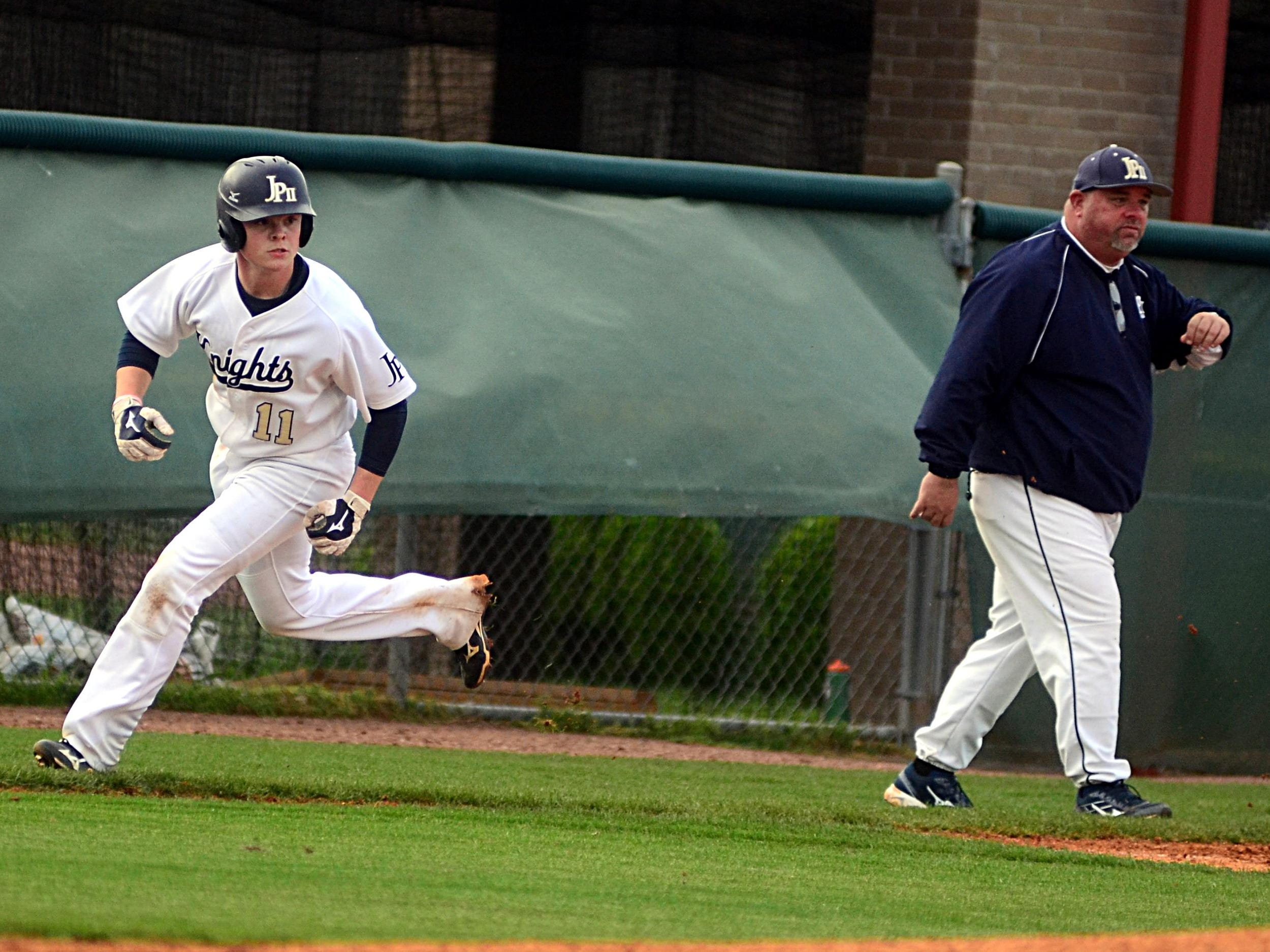 Pope John Paul II High senior Garrett Taylor rounds third base as head coach Michael Brown gives directions during game one of Friday evening's doubleheader.