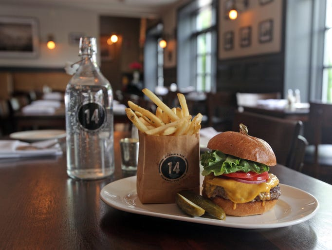 Saturday Night Burger with cheese, lettuce tomato and paper bag fries is served at 14 and Hudson kitchen and bar in Piermont on June 10, 2014.