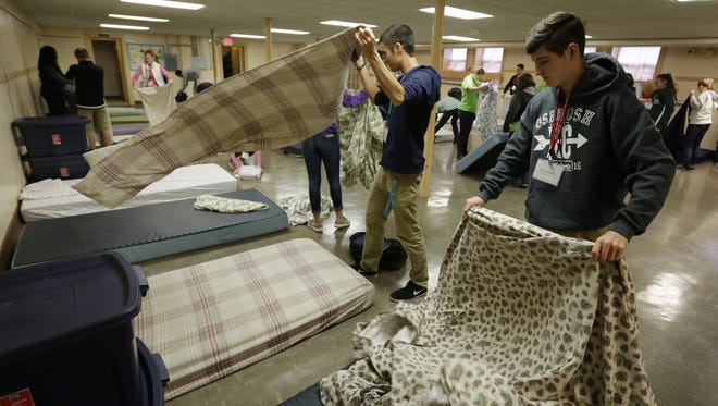 High school students Will Scheuermann of Oshkosh West and Daniel Colombana of Oshkosh North strip mattresses and fold sheets and blankets to put into a pillow case at the Day by Day Warming Shelter. The Youth Leadership Oshkosh class visited the shelter as part of its Health and Human Services module and learned about homeless in Oshkosh.