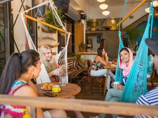Diners sit in hammocks at the Drift Sidewalk Café &