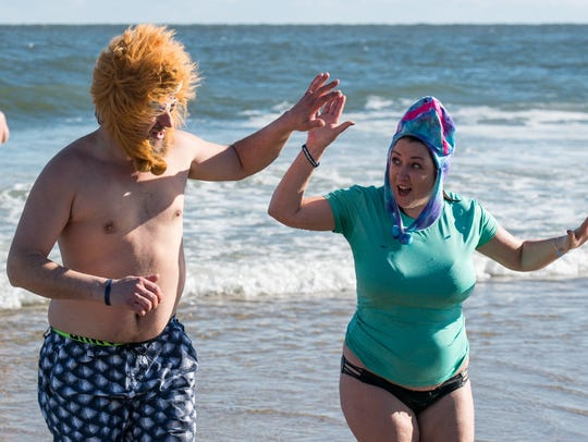 Two swimmers high five after plunging in the ocean during the 24th Annual Penguin Swim near the Princess Royale Hotel in Ocean City on Monday, Jan. 1, 2018.