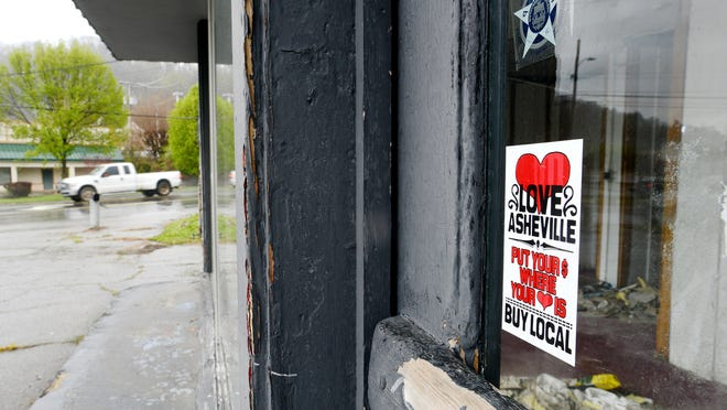 A sticker promoting a campaign to buy local is still attached to the door of an unnamed vacant business that at one time was a gas station along Tunnel Road on Tuesday. Some worry that as downtown continues to boom this area of the road is being left behind.