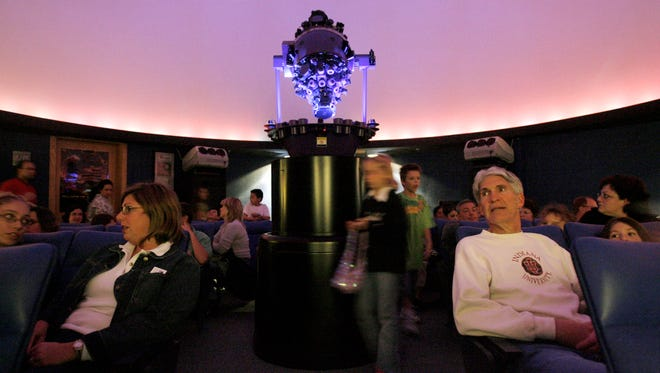 Visitors wait for the lights to go down in the planetarium at Carmel High School.