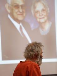 Jeffrey Maurer, 54, sits under a photograph of his