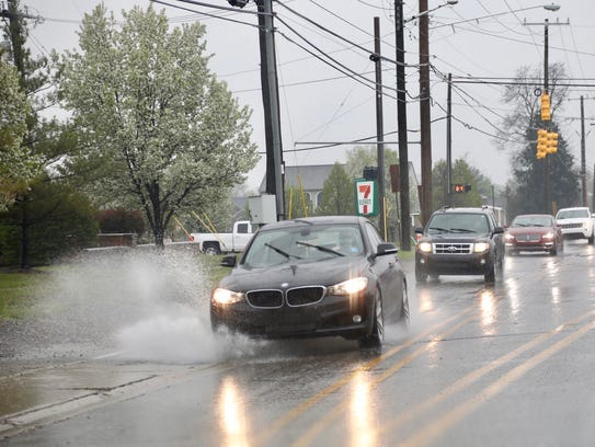 Cars hit puddles of water as they drive down Dequindre