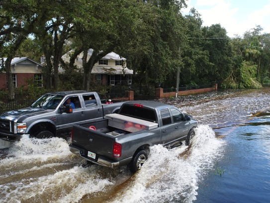 Residents drive through flooded streets Tuesday, Sept.