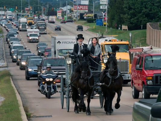 Joe Tetz, left, of Shartlesville rides with Jeannie Williams of Charlotte, NC, with her father Carlton W. Lizotte carried in the horse drawn hearse that was built in 1913 behind them on Route 30 near Pennsylvania Ave in York Tuesday September 22, 2015  Paul Kuehnel - York Daily Record/ Sunday News