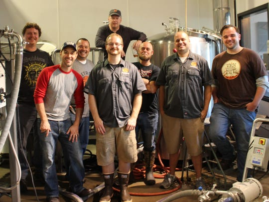 Brent Raymond (second from left), founder of Facebook group Detroit Area Craft Beer Enthusiasts, stands for a photo with group members and Old Nation Brewing Co. staff, including co-owner Travis Fritts (far right) Sept. 24, 2016 at the brewery in Williamston.