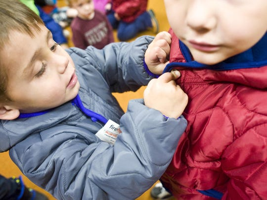 Kaiden Hersey, 3, helps Cyler Doney-Huskins 4, button his coat during an Operation Warm event for Head Start children at Skyline School on Tuesday.