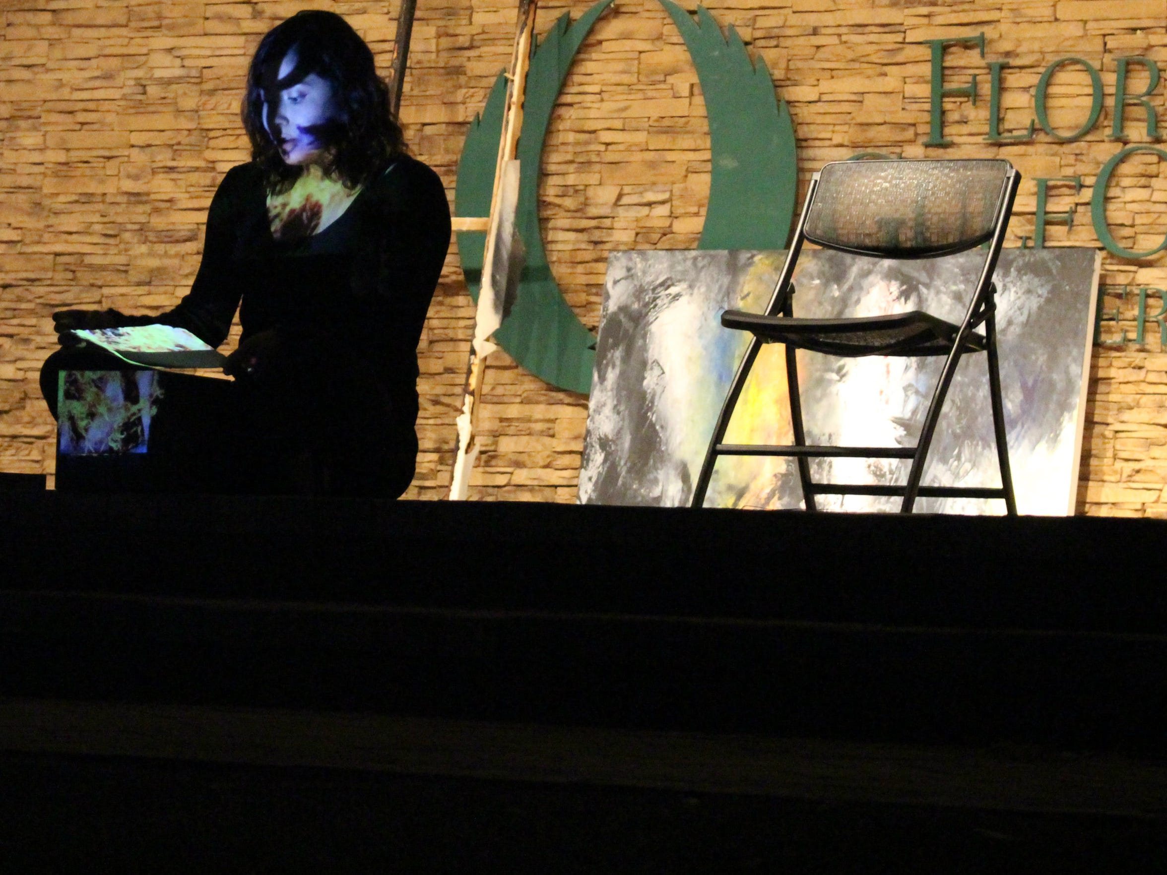 "Florida Gulf Coast University student Sasha Cardenas performs a transcript called ""The Burning Box"" during a S(he) Will Fade performance. A painting is being projected onto her face."