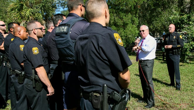 "In this Wednesday, Oct. 25, 2017 photo, Mayor Bob Buckhorn, center right, addresses members of the Tampa Police Department while Interim Police Chief Brian Dugan, right, looks on during a roll call and press conference at Giddens Park in the Seminole Heights neighborhood in Tampa, Fla. Buckhorn told police officers looking for a suspect in three fatal and apparently random shootings in the neighborhood to hunt him down and ""bring his head to me.""  (Gabriella Angotti-Jones/Tampa Bay Times via AP)"