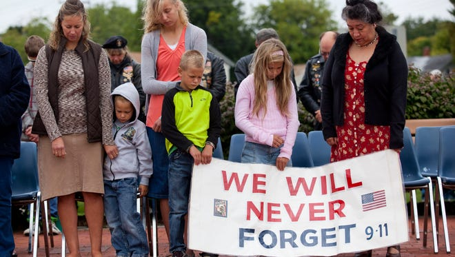 Jenny Frazier, Samuel Frazier, 4, Alesia Frazier, 14, Josiah Frazier, 6, Evie Frazier, 8, and Irene Michels rest their heads in a moment of silence during a ceremony to remember those who died in the attacks on 9-11 Thursday at International Flag Plaza in Port Huron.