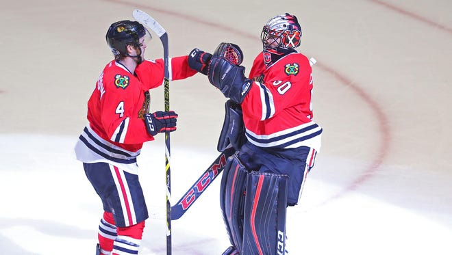 Chicago Blackhawks goalie Corey Crawford (right) is congratulated by  defenseman Niklas Hjalmarsson (left) following the conclusion of the third period in Game 6.