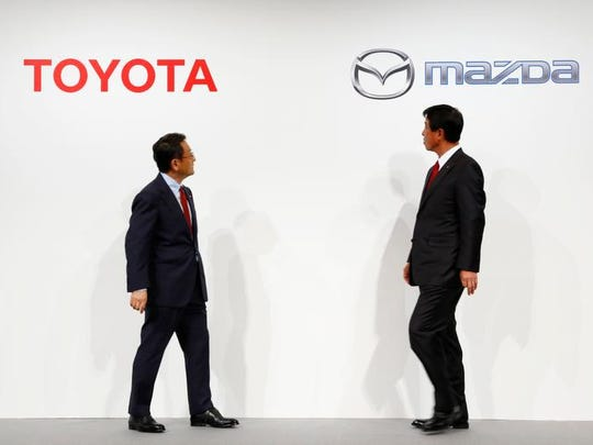 Toyota Motor Corp. President Akio Toyotda, left, and Mazda Motor Corp. President Masamichi Kogai look at their companies logos after a press conference in Tokyo on May 13 2015. Toyota and Japanese rival Mazda are expanding their partnership to a long-term one focusing on technologies in the areas of safety and efficiency.