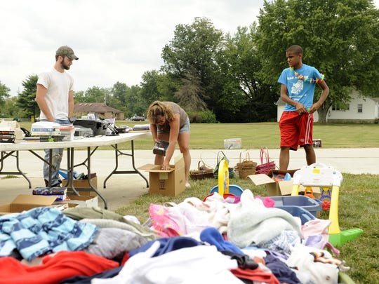 Josh Naylor, Loretta Naylor and Mac Croom pack up donated items after a garage sale to benefit Autism Speaks. Mac found several small toys that he attempted to secret away without others noticing, though his bulging pockets gave him away.