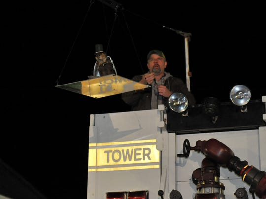 Marshall P. Muskrat prepares for a ride on the zip line with a little help from Ronnie Haymaker during the annual Muskrat Dive New Year's Eve celebration in downtown Princess Anne.