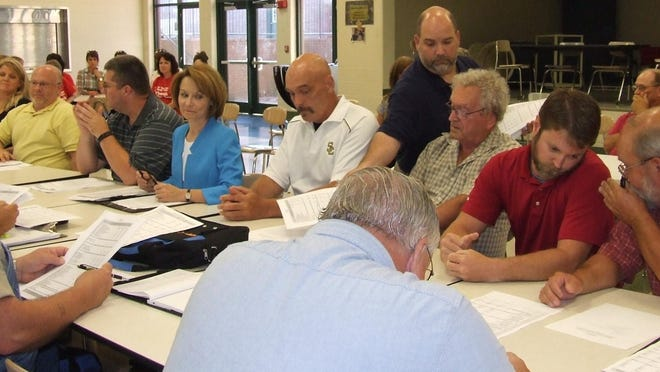 Flashback: Stewart County Schools Payroll and Finance Director Jamie Bogard passes out budgets to members of the county Budget and Finance Committee as they informally chit-chat before the actual discussion on July 16.