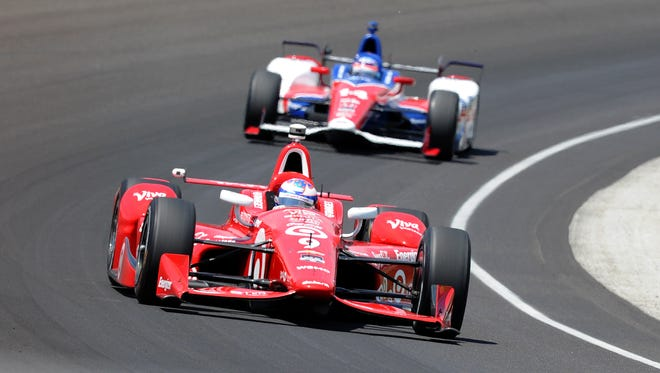 Chip Ganassi Racing driver Scott Dixon (front) navigates his car through Turn One at Indianapolis Motor Speedway during the Indianapolis 500 on May 23, 2015.