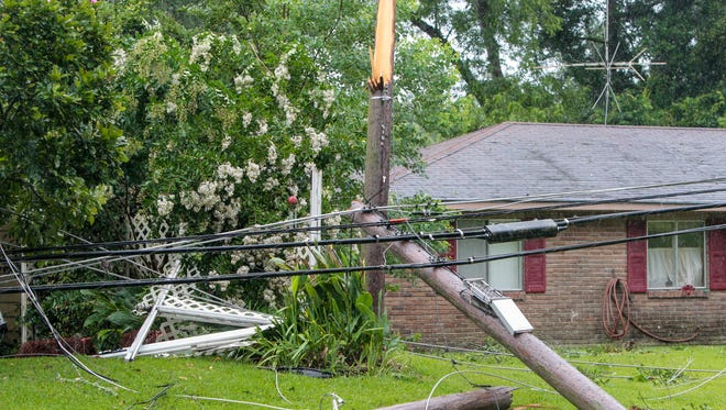 Trees and downed power lines sit in the yards of houses in Liberty, Miss., Tuesday, June 10, 2014. A strong storm line passed through southwest Mississippi, toppling trees and power lines, leading to power outages and traffic disruptions, as well as causing minor property damage throughout the area. (AP Photo / The Enterprise-Journal, Daniel Lin)