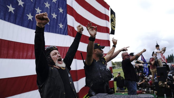 Members of the Proud Boys cheer on stage as they and other right-wing demonstrators rally on Saturday, Sept. 26, 2020, in Portland, Ore.