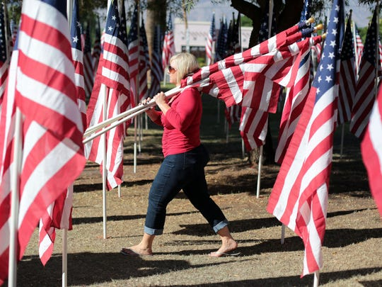 Volunteers post flags for the Healing Field display on the corner of Dinah Shore and Date Palm Dr. in Cathedral City on Saturday, November 8, 2014. Over 100 volunteers posted  5100 flags to pay tribute to veterans.