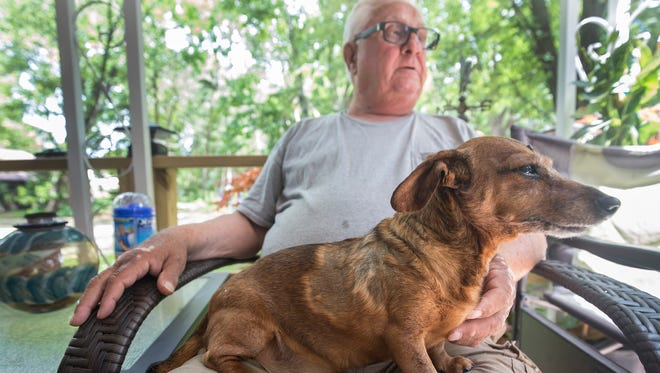 Steve Payok, 73, of Warren holds his daughter's dog Bella, a 14-year-old mini dachshund, on Wednesday. Bella is recovering following two surgeries since she was attacked by a coyote outside her Warren home in the early morning of Jan. 25, 2018.
