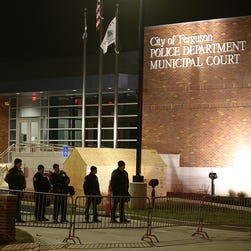 Police officers stand guard in front of the Ferguson (Mo.) Police Department on Monday.