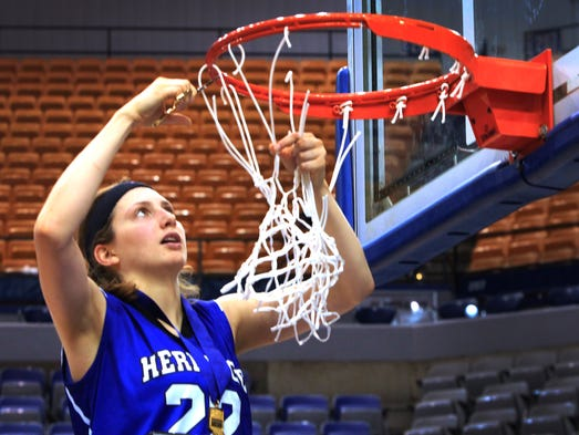 Heritage Christian's Natalie Orr cuts down the net after the Eagles' 64-61 state championship victory over Fort Wayne Canterbury in IHSAA Class 2A at the Hulman Center in Terre Haute on Saturday, March 8, 2014. Orr was the Mental Attitude Award winner.