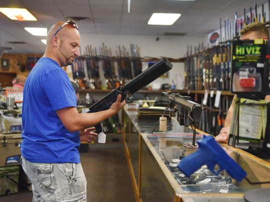 David Bram, gun owner, looks at guns at Gary's Gun Shop Friday. Bram had some time to kill and decided to browse the store.