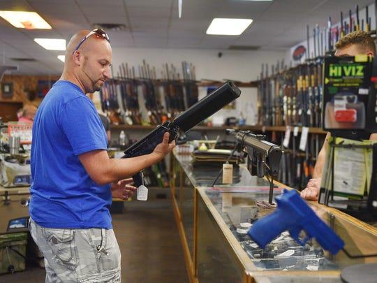 David Bram, gun owner, looks at guns at Gary's Gun